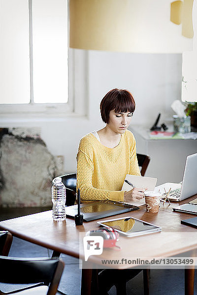 Businesswoman writing notes while working desk in creative office