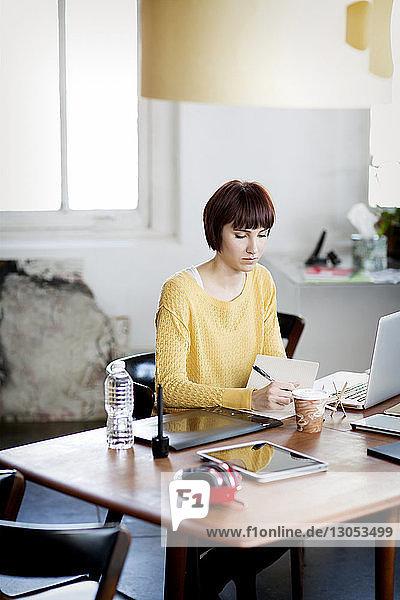 Geschäftsfrau schreibt Notizen am Schreibtisch im Kreativbüro