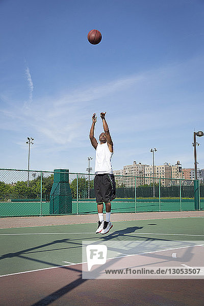 Man playing basketball in court on sunny day