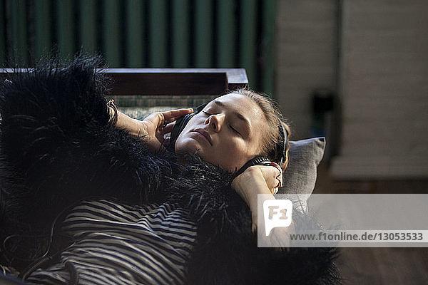 Nahaufnahme einer Frau  die Musik hört  während sie zu Hause auf dem Sofa liegt