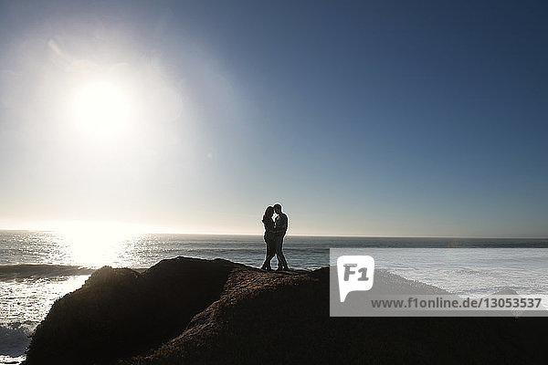 Ehepaar steht auf einem Felsen am Meer gegen den Himmel an einem sonnigen Tag