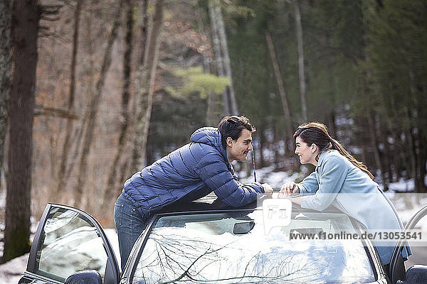 Glückliches Paar lehnt sich an Auto an