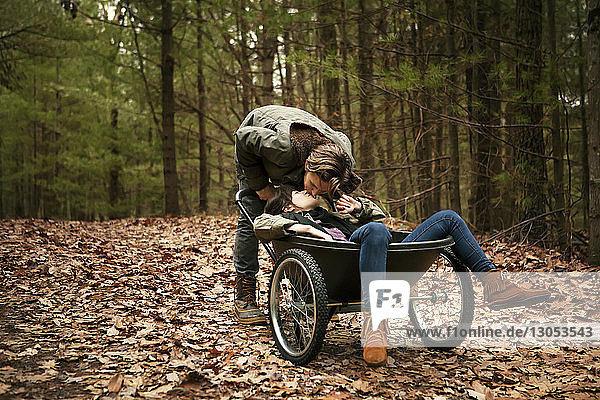 Man kissing woman sitting on wheelbarrow in forest