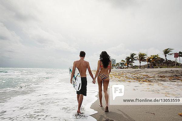 Rückansicht eines Paares  das sich beim Spaziergang am Meeresufer vor bewölktem Himmel an den Händen hält
