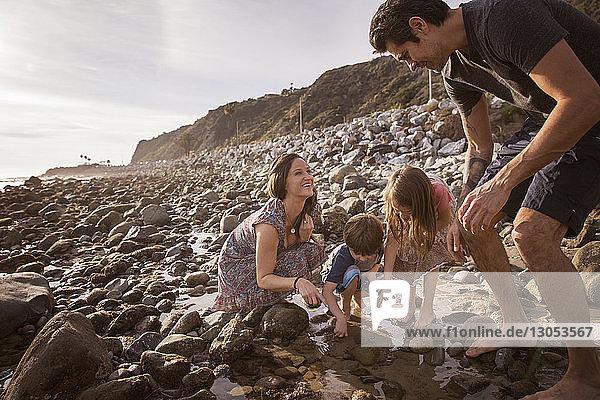 Glückliche Familie genießt am Strand bei Sonnenuntergang