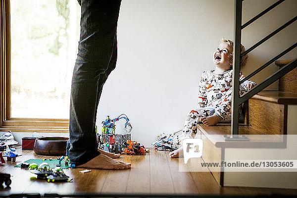 Glücklicher Junge sitzt auf der Treppe  während er den Vater zu Hause anschaut