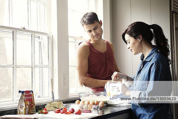 Frau bereitet das Essen vor  während der Mann auf der Küchentheke sitzt