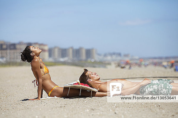 Side view of couple relaxing at beach against blue sky