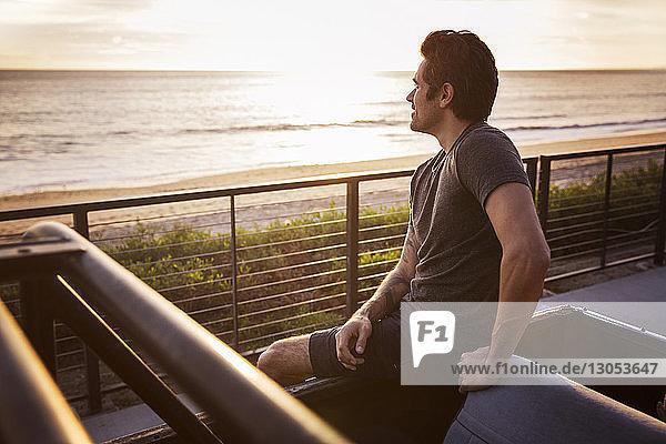 Mann schaut weg  während er bei Sonnenuntergang auf einem Pick-up sitzt