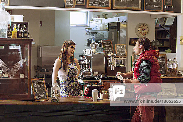 Female owner looking at customer while standing by counter in cafe