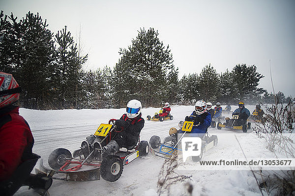 People enjoying go-carts racing on snow covered field