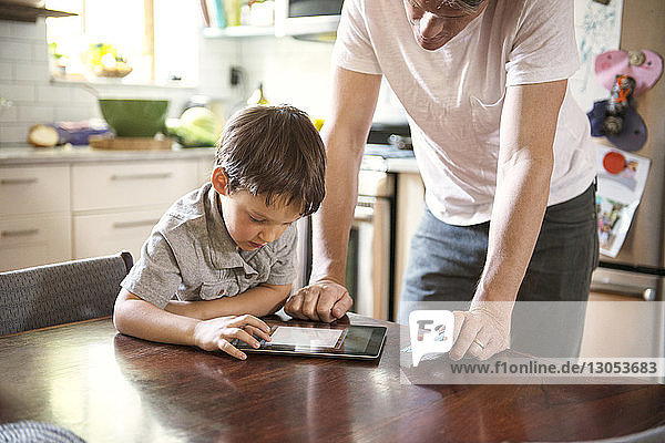 Father assisting son in using tablet computer at home