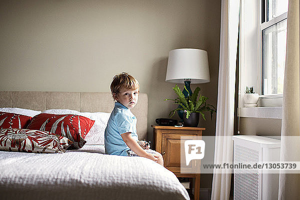 Portrait of boy sitting on bed in room