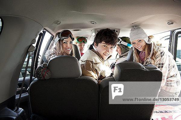 Porträt von glücklichen Freunden im Auto sitzend