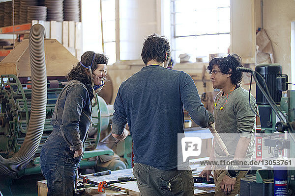Carpenters discussing in workshop