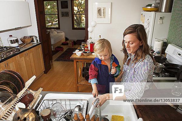 Mutter und Sohn waschen Utensilien in der häuslichen Küche