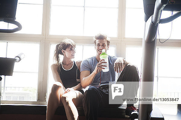 Mann trinkt Wasser  während Frau ins Fitnessstudio schaut