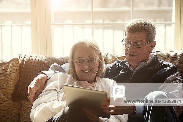 Senior couple using tablet while sitting on sofa at home