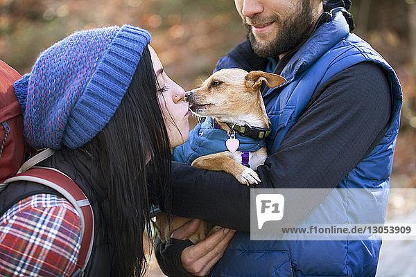 Frau küsst Hund  der von ihrem Freund gehalten wird  während sie auf dem Feld steht