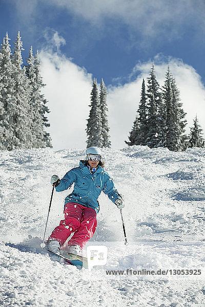 Glückliche Frau beim Skifahren am Berg