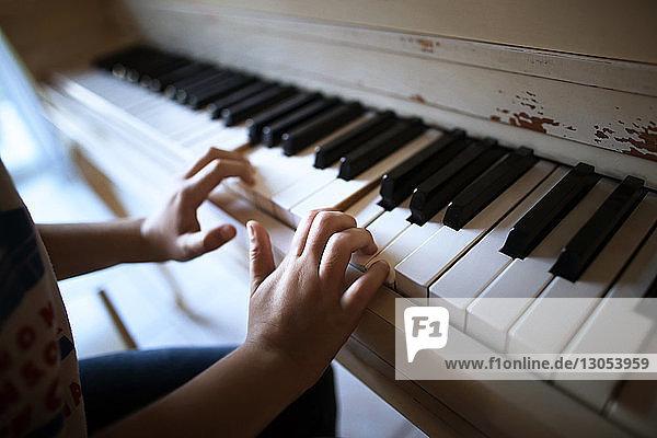 Close-up of boy playing piano at home