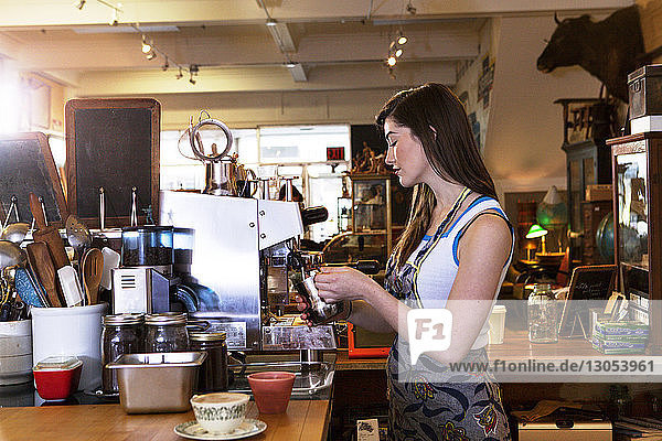 Side view of female owner working at coffee shop
