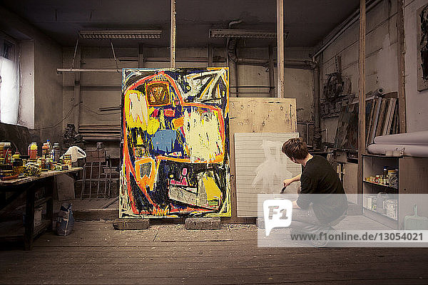Man crouching while painting on wood at workshop