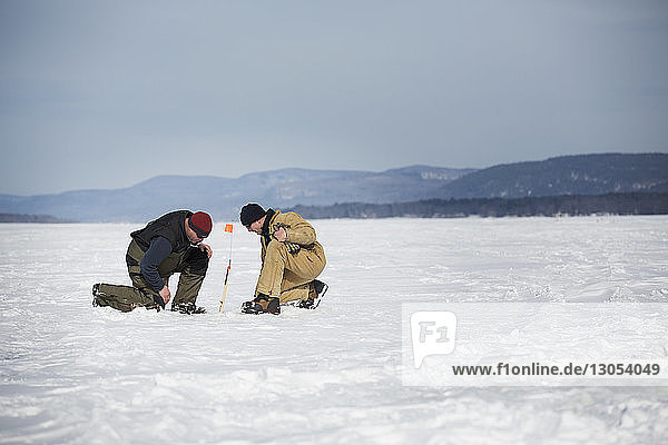 Side view of men ice fishing on frozen lake against sky
