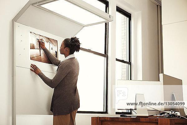 Frau schreibt im Amt stehend auf Karte