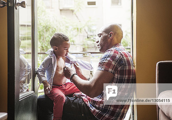 Father dressing son while sitting at entrance