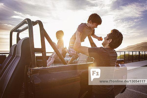 Mann hebt Jungen bei Sonnenuntergang vom Pick-up
