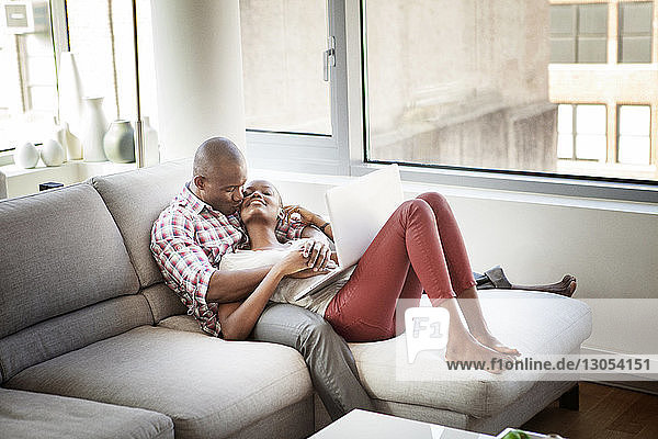 Man kissing woman while relaxing on sofa at home