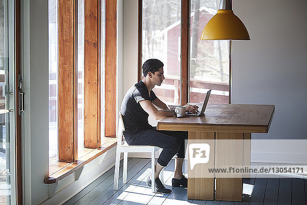 Side view of man using laptop computer while sitting on chair by table at home
