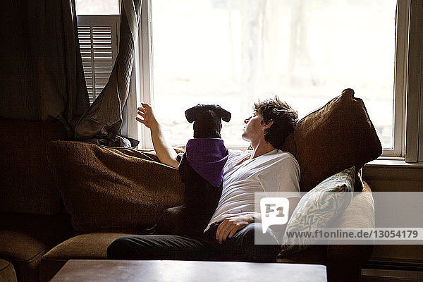Man and dog looking through window while sitting on sofa at home