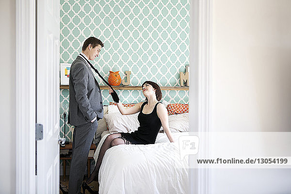Passionate woman pulling man's necktie in bedroom at home