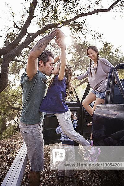 Vater küsst Tochter von Familie im Wald