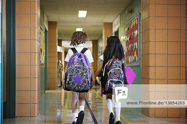 Rückansicht von Schulmädchen auf dem Flur