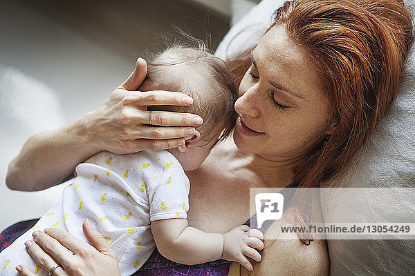 High angle view of mother embracing baby girl