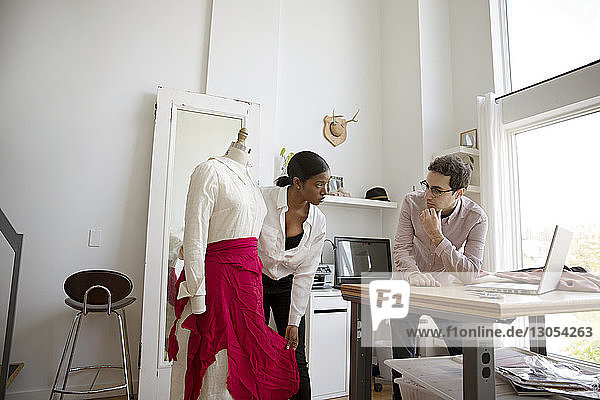 Fashion designer showing dress on model to colleague
