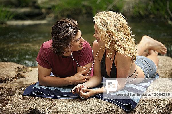 Couple listening music while lying on rocks at riverbank