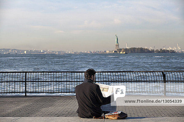 Man reading news paper while sitting on promenade against Hudson River