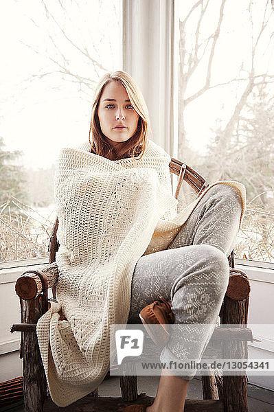 Porträt einer selbstbewussten  in eine Decke gehüllten Frau  die auf einem Stuhl sitzt