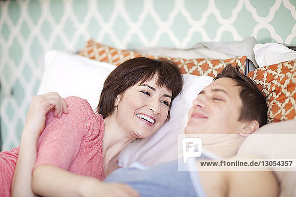 Happy couple lying on bed at home