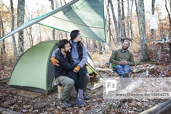 Freund schaut Paar an  während er auf Baumstümpfen sitzend am Zelt im Wald