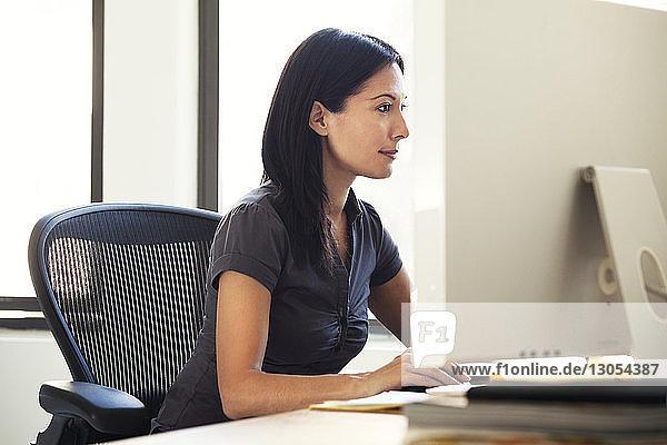 Geschäftsfrau benutzt Computer  während sie im Büro auf einem Stuhl sitzt