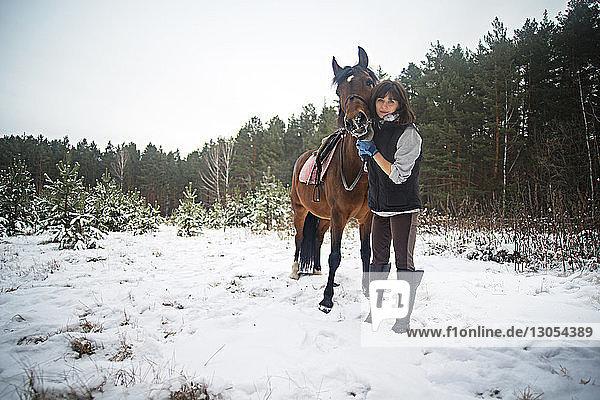 Frau und Pferd stehen auf schneebedecktem Feld