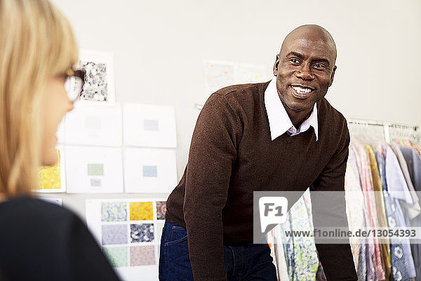 Male fashion designer looking at colleague in workshop
