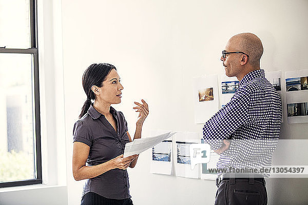 Businessman and businesswoman discussing while standing against wall in office