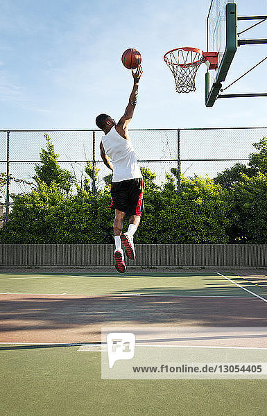 Rear view of sportsman dunking ball in hoop at court