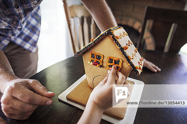 Cropped image of boy decorating gingerbread house at home